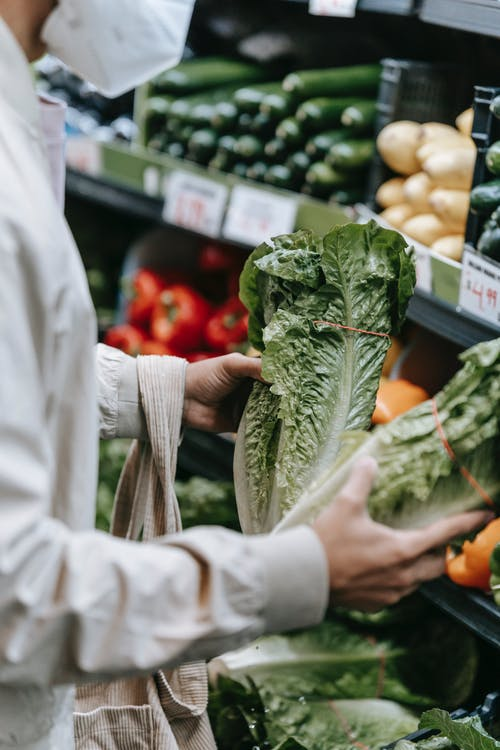 Crop anonymous buyer in protective mask with shopping bag choosing fresh greens while standing near stall with vegetables in grocery store