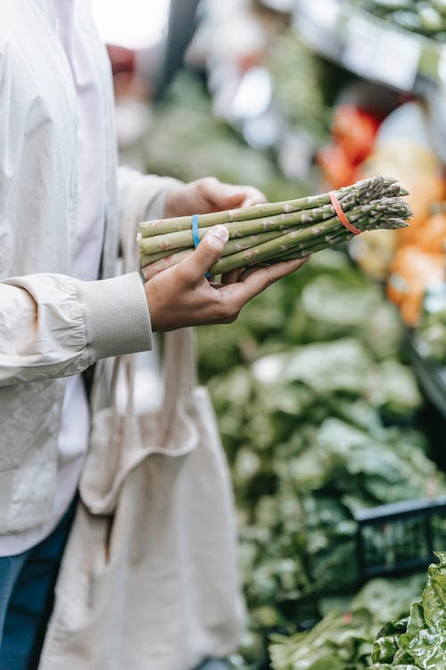 Crop faceless customer with green asparagus in hands standing near stall with fresh greens on blurred background during grocery shopping