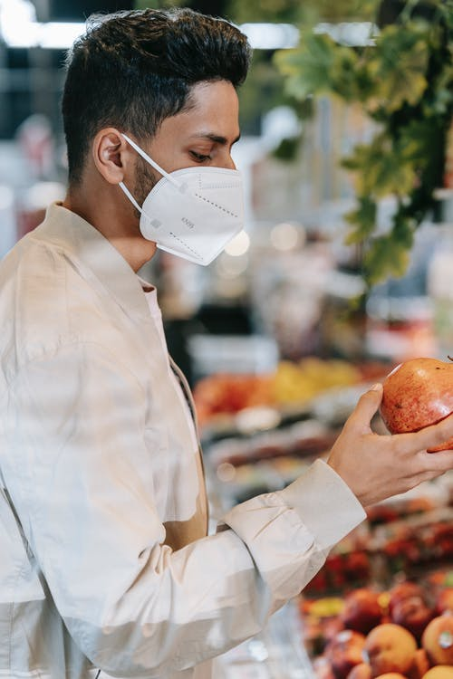 Side view of young ethnic concentrated male millennial in stylish clothes and protective mask selecting ripe pomegranate during shopping in grocery market