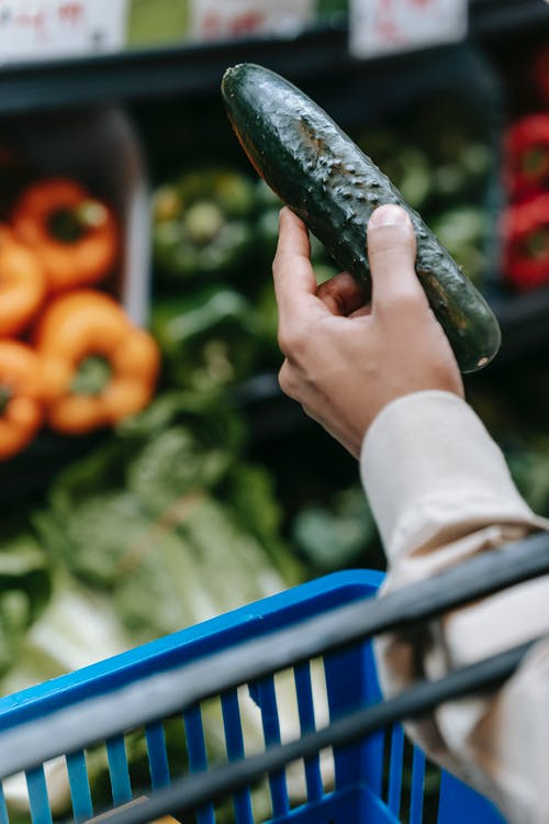 Crop anonymous man holding shopping basket and choosing fresh cucumber during purchases in modern supermarket