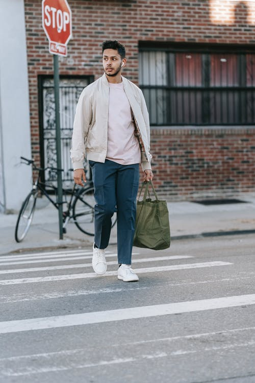 Trendy ethnic man with natural bag crossing urban road