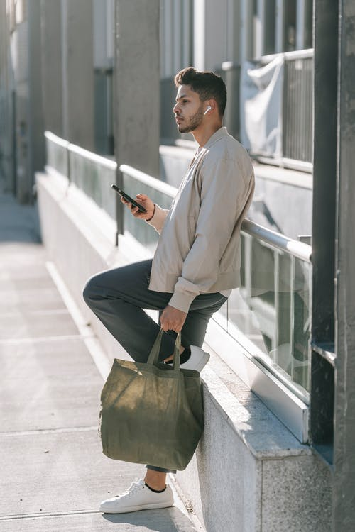 Trendy Indian man with smartphone and eco bag in town