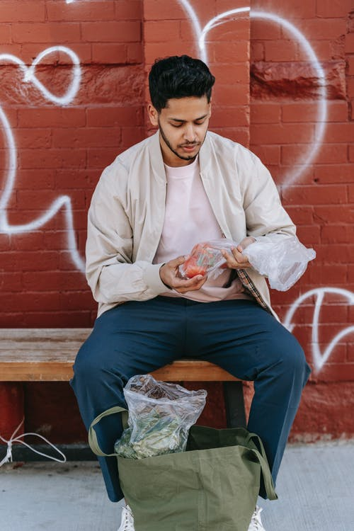 Trendy ethnic male sitting on bench with fresh vegetables between eco bag and brick wall on street