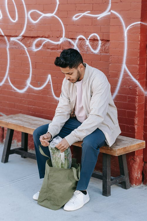 Stylish young Indian male with modern haircut sitting on bench with eco bag and fresh green vegetables in town