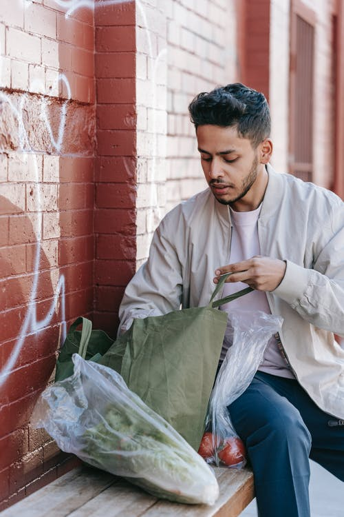 Trendy ethnic man with fresh vegetables and natural bag