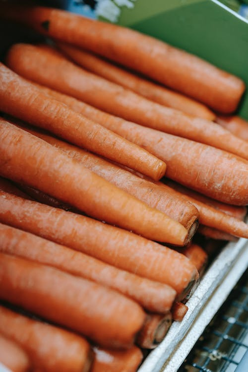 Healthy product of raw carrots with dry peel in rows in box on blurred background