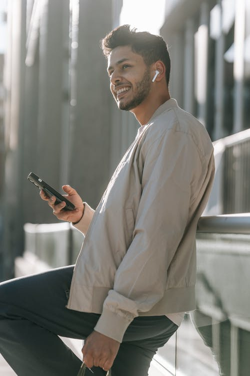 Side view of cheerful ethnic male in trendy wear with cellphone enjoying music from wireless earbud while looking away outdoors