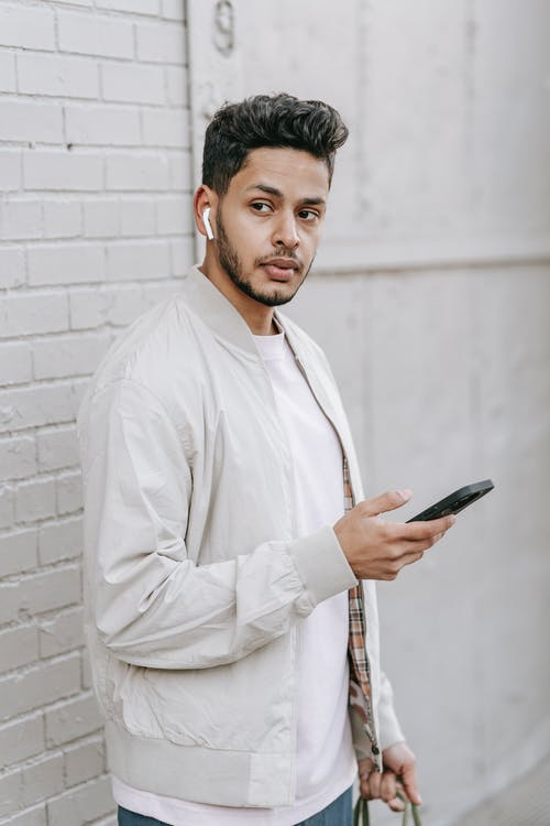 Dreamy young ethnic male with modern haircut and cellphone listening to music from wireless earbud while looking away against brick wall