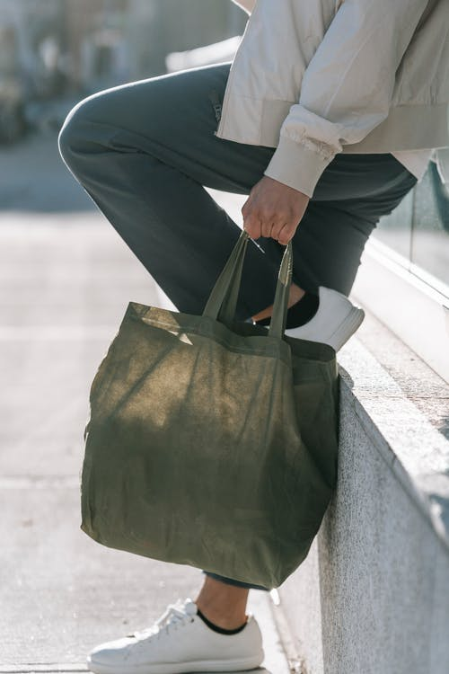 Side view of crop anonymous male in trendy clothes with natural bag and raised leg standing on urban pavement