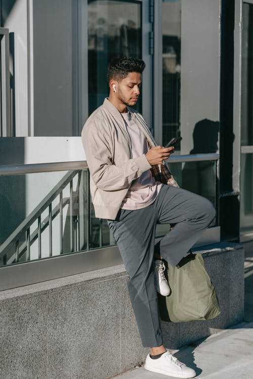 Stylish ethnic male with natural bag listening to music from earbud while browsing internet on cellphone in city