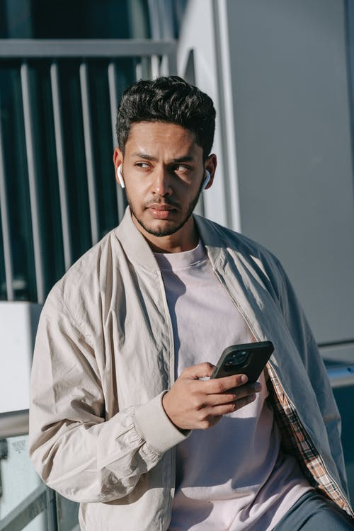 Dreamy young Indian male with cellphone listening to music from wireless earbuds while looking away on street