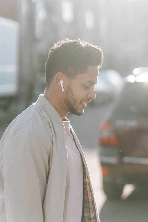 Trendy Indian man listening to song from earbud on road