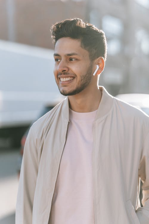 Smiling ethnic man listening to song from earbud on street