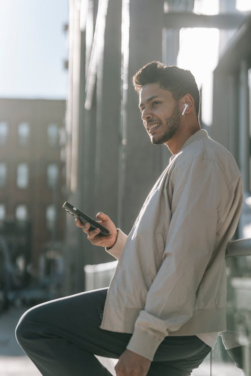 Side view of smiling ethnic male with modern haircut and cellphone looking away while listening to song from earbud outdoors