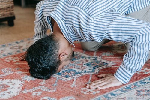 Man in Blue and White Stripe Dress Shirt Bowing Down on Red and Blue Area Rug