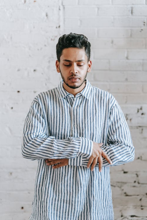 Man in White and Blue Striped Dress Shirt Standing Near White Wall