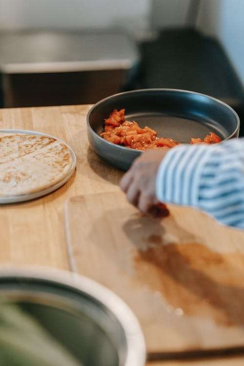 Crop unrecognizable ethnic male at table with chopping board against flatbread and cut fresh tomato in bowl at home