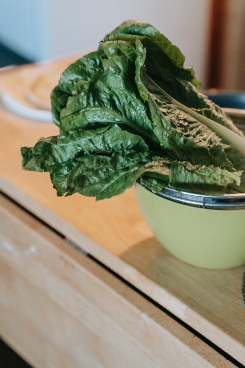 Fresh lush spinach foliage in bowl on wooden table in house on blurred background
