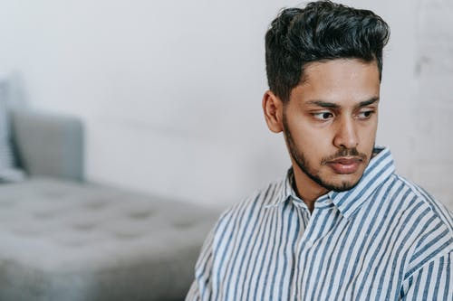 Lonely Indian man in striped shirt at home