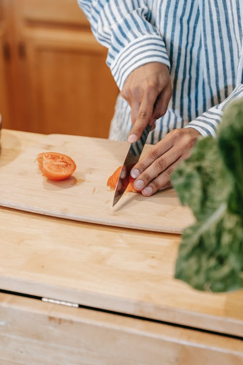 Crop ethnic man cutting fresh tomato while cooking at home