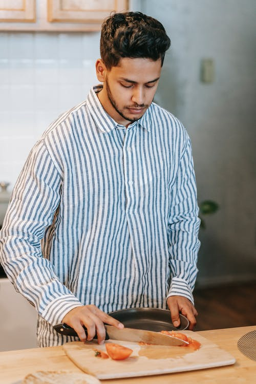 Young ethnic male in striped shirt with bowl and knife against chopping board with cut fresh tomato at home