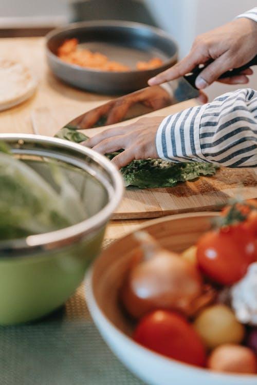 Crop man cutting fresh spinach on chopping board in kitchen