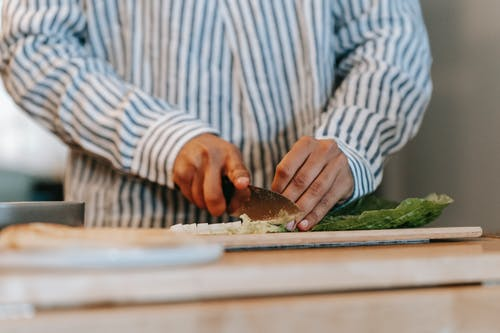 Crop anonymous male cook in striped shirt cutting fresh green lettuce leaves on wooden board while preparing dinner in kitchen