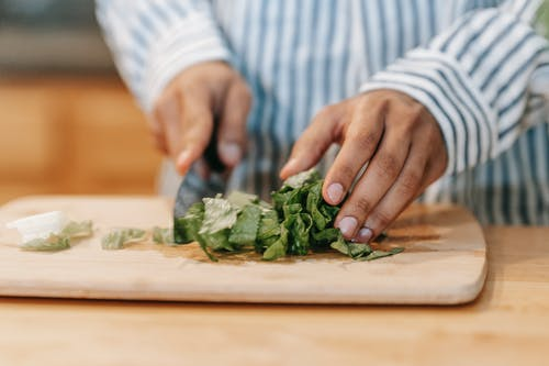 Crop man cutting green leaves while preparing healthy food in kitchen
