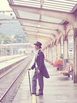 Sepia Effects Photo of Man in Black Tuxedo Standing on Train Station during Daytime