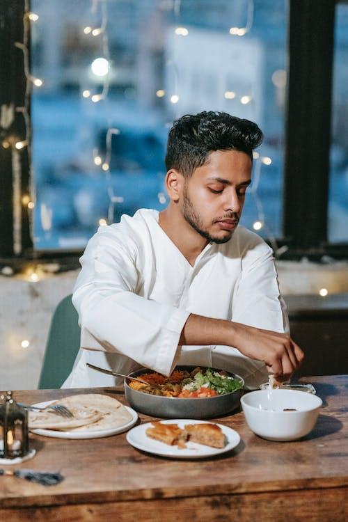 Man in White Dress Shirt Eating Food