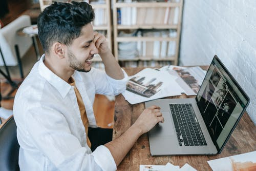 Positive ethnic male working on laptop in room