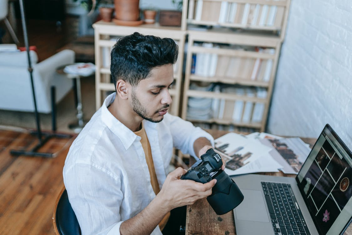 Side view of Indian male photographer in casual clothes watching photos on photo camera while sitting at table and browsing laptop at home in daytime