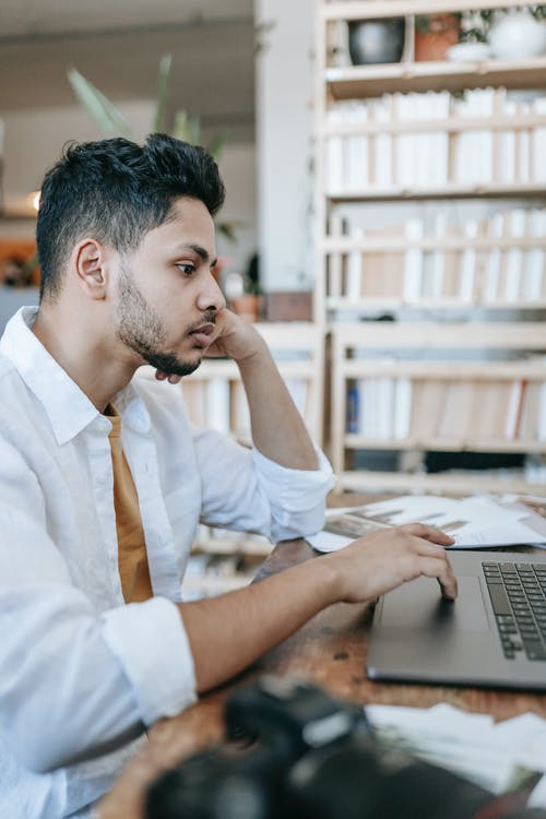 Concentrated ethnic male sitting at table and working on laptop
