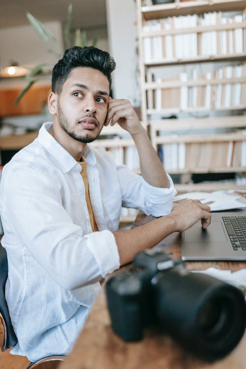 Pensive young ethnic guy in white shirt at wooden table with professional photo camera and netbook while looking away in light apartment