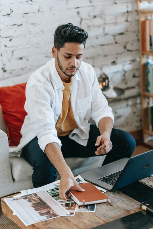 Young Hispanic male designer taking planner from table with laptop and pictures while working on project in modern loft style workplace