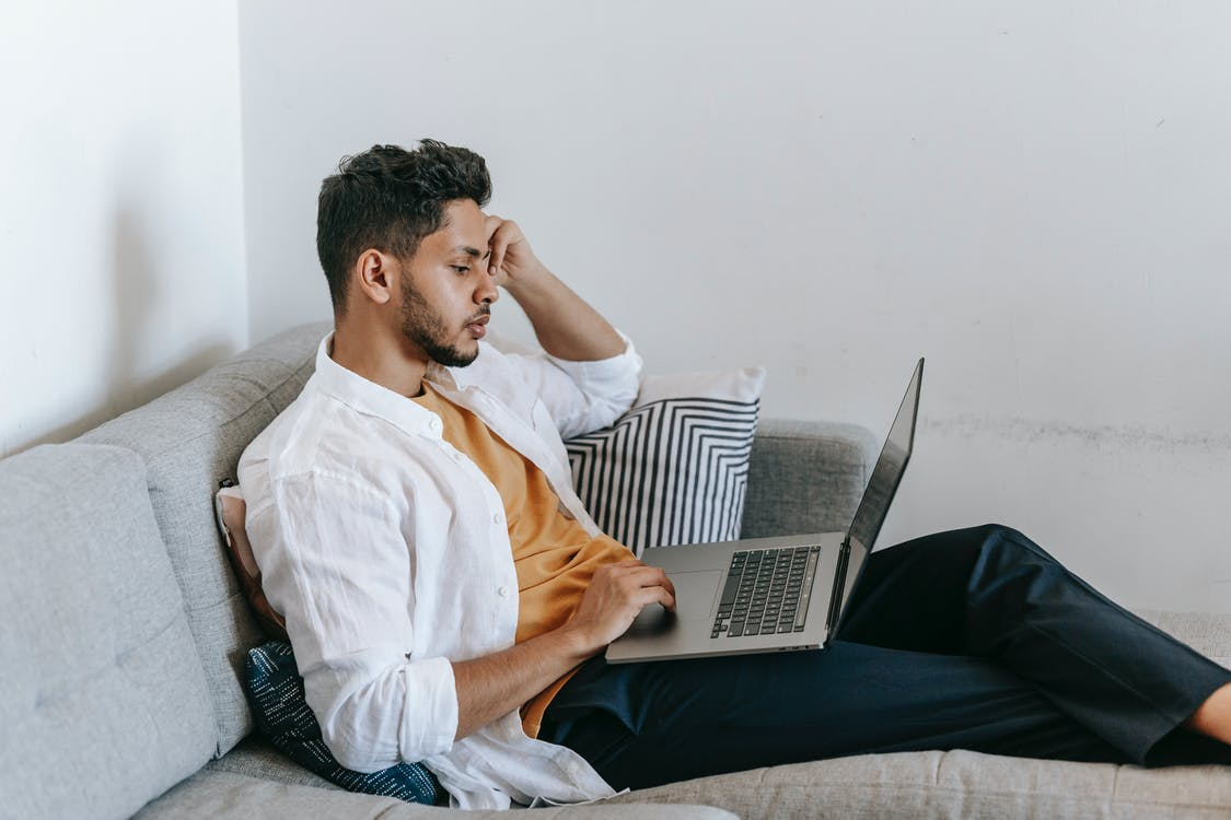 Side view of serious young Hispanic male remote employee sitting on sofa and using laptop while working distantly from home