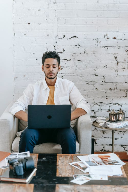 Young Hispanic male travel blogger creating content for social media on laptop while working in modern loft style room with photo camera and pictures on table