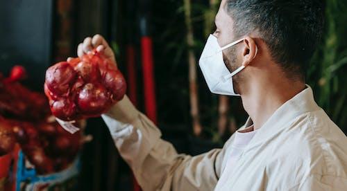 Man in mask choosing grocery in store