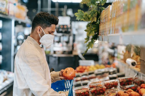 Side view of young Hispanic man in protective mask choosing fresh pomegranate from stall in supermarket during coronavirus pandemic