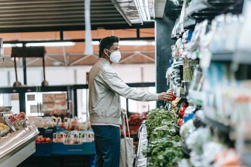 Man in mask choosing fresh groceries in store