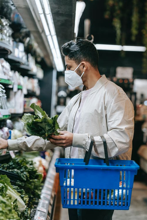 Side view of young ethnic male buyer in protective mask with shopping basket picking fresh green leaves from shelf in supermarket while doing purchases during coronavirus pandemic
