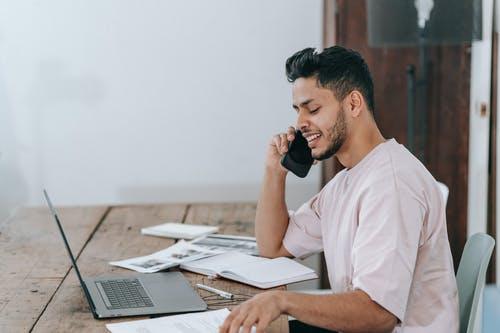 Happy businessman speaking on phone at workplace