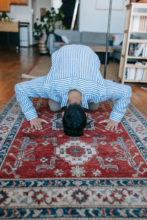 Man in Blue and White Striped Shirt Bowing Down on Red and Blue Area Rug