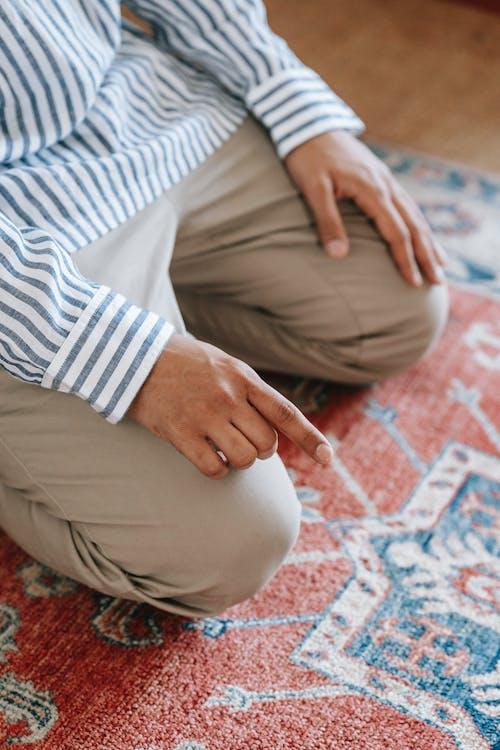Man Wearing Brown Pants Kneeling on Red Rug