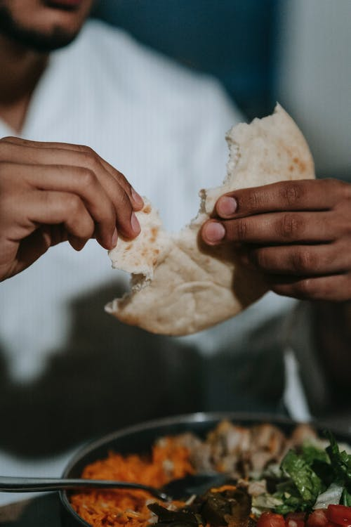 Person in White Dress Shirt Holding White Bread