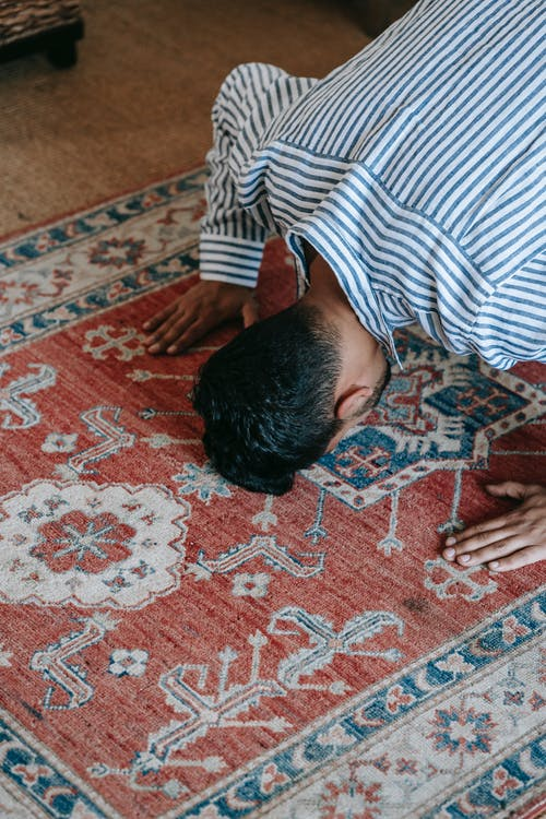 Man in Blue and White Striped Shirt Bowing Down on Red and White Area Rug