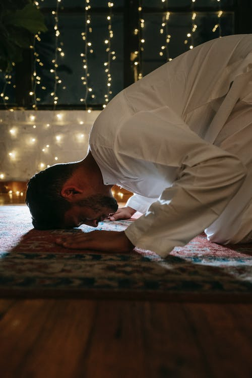 Man in White Thobe Bowing Down on Red and Blue Rug