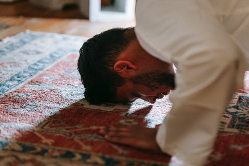 Man in White Dress Shirt Bowing Down on a Rug