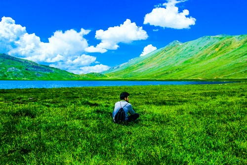 Boy Sitting on Green Grass Field
