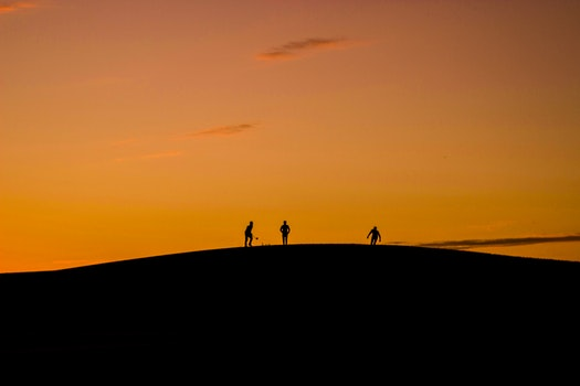 Silhouette of 3 People in Hill during Sunset